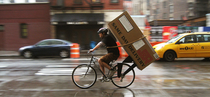 delivery man on a bike with big box on his back